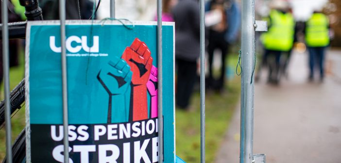 """A UCU strike ballot poster attached to railings, with the text """"USS Pension Strike"""""""