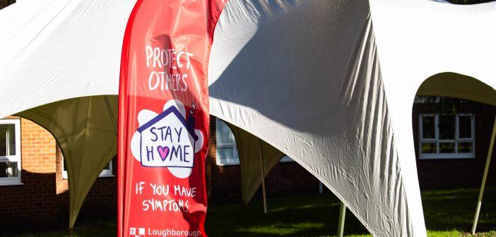 Banner outside Telford Hall telling students to protect others and stay at home if they have coronavirus symptoms