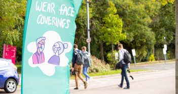 green banner on Loughborough campus telling students to wear face coverings