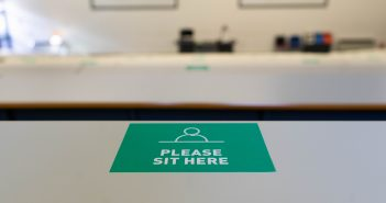 sticker on a lecture theatre desk saying 'please sit here'