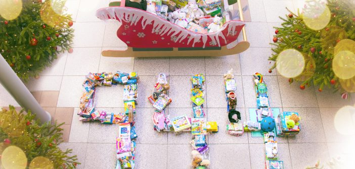 Christmas presents arranged on the floor to resemble the number 944, next to a sleigh