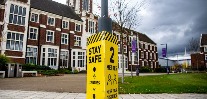 Yellow Coronavirus lamppost sign in front of Loughborough's Hazlerigg building