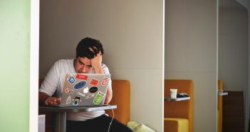 A person looking stressed whilst looking at their laptop