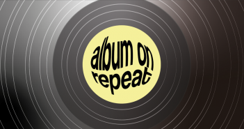 """Black record disc as the background, with a yellow centre and the text """"album on repeat"""" in black"""
