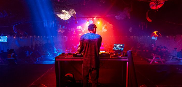 DJ central in the middle of the photograph on a SU club night with blue and red disco lights.