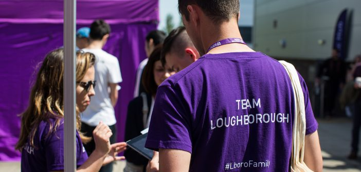 """A student wearing a """"team Loughborough' shirt helps parents on an open day"""